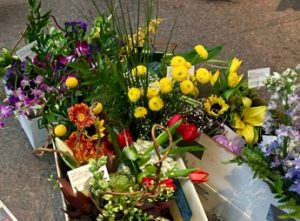 Boxes of AfterBloom bouquets ready for delivery by volunteers. The card reads: Our gift to you: Art that Blooms.